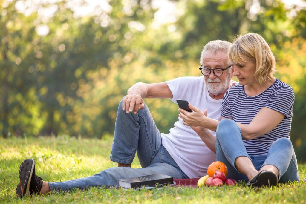 Happy,Senior,Couple,Relaxing,In,Park,Using,Smartphone,Together,.